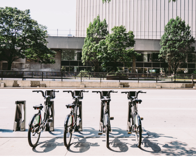 four bikes in a bike share parking next to a street