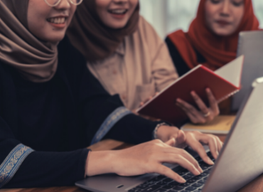 A group of working together with a laptop and books