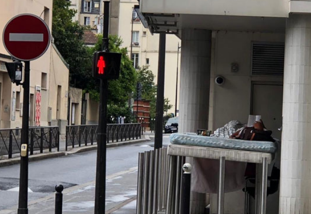 A homeless person reading a book on a mattress propped up on poles in a street corner  next to a traffic signal