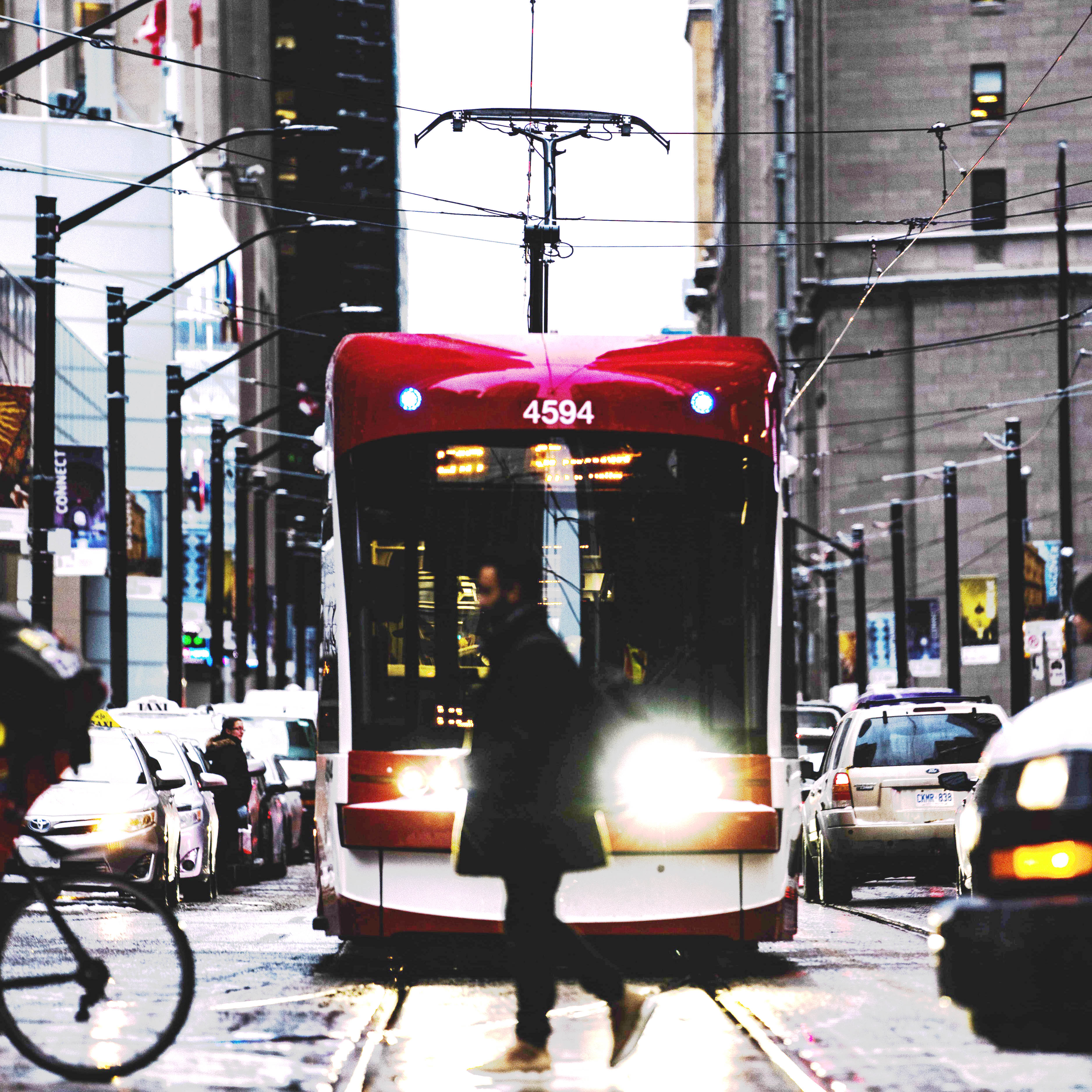 A pedestrian passing by in front of a TTC street car during daytime.