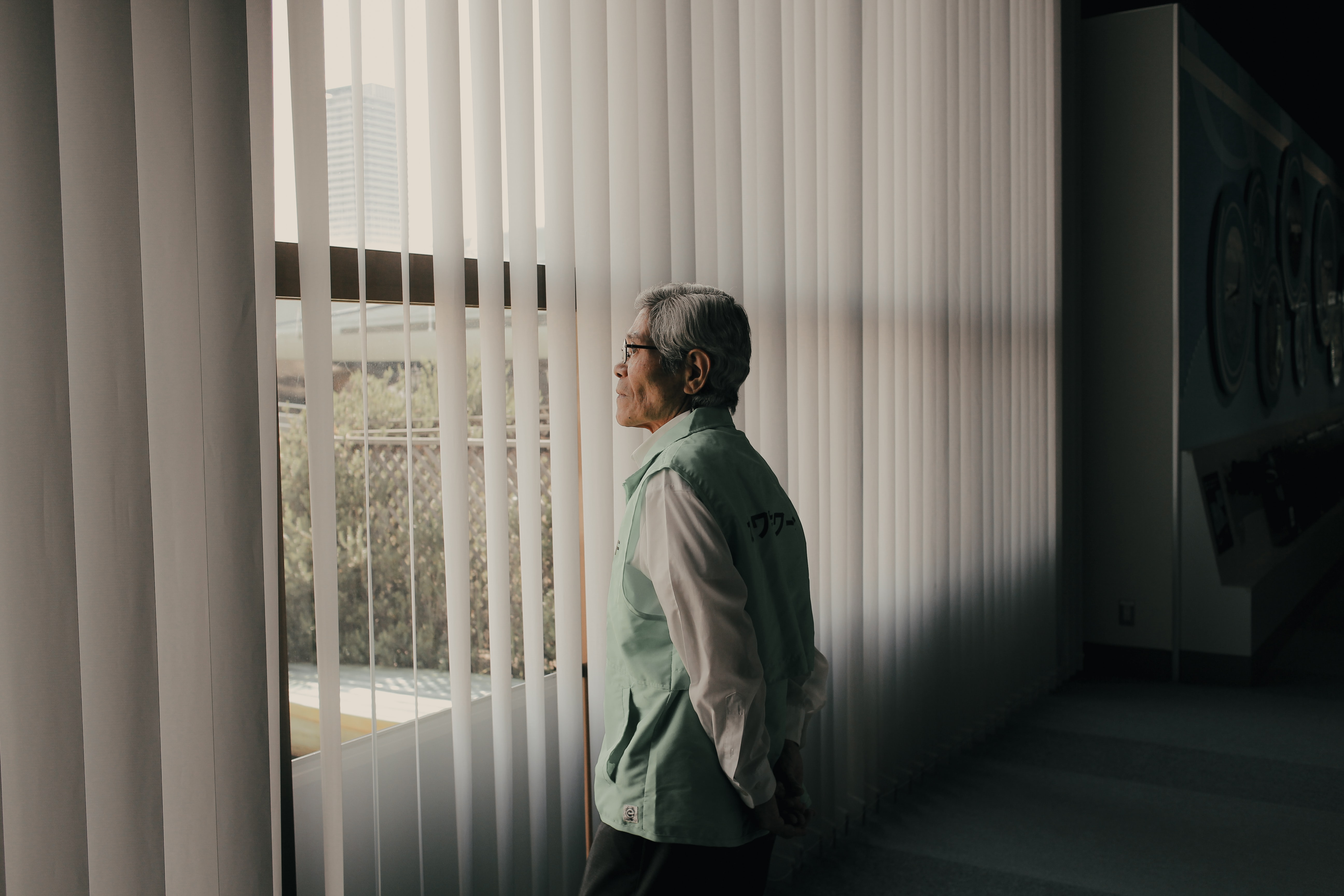 An older Asian gentleman looking our of the window in a long term care home