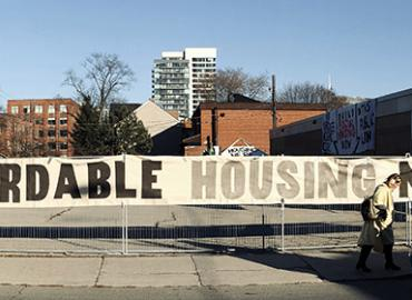 "A sign in front of a parking lot reads ""Affordable Housing Now"""