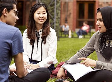Three U of T students sitting in the Munk School of Global Affairs and Public Policy courtyard