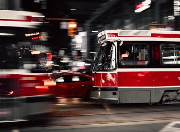 Image of TTC streetcars in motion after dark